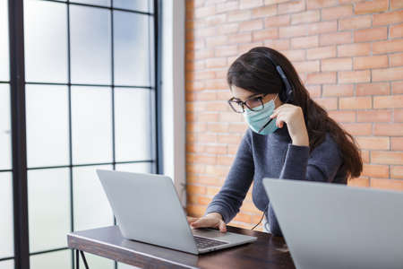 young beautiful women call center wear headset and mask working with laptop while consulting customers with online problems. support operator service business representative concept. online marketing