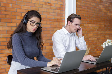 young women and man call center wear headset and working with laptop while consulting customers with online problems. support operator service business representative concept. online marketing