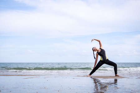 young Asian woman is stretching or warm-up her body in yoga pose before exercise by running on the beach female fitness model portrait. Concepts of exercise and good health. Standard-Bild