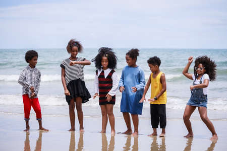 Funny vacation. Children or kids playing and romp together at the beach on holiday. Having fun after unlocking down the city from COVID19. Seven African American kids. Ethnically diverse concept Standard-Bild