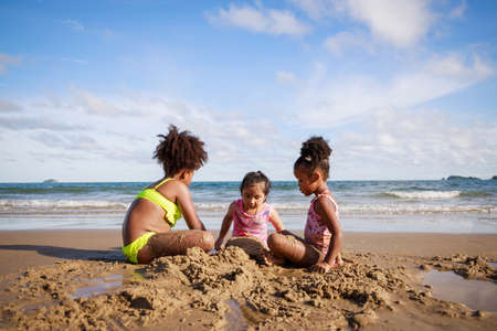 Happy friendship. Happy vacation holiday. Happy three African American kids are building a sandcastle on tropical beach and have fun together in summer. Relaxation in vacation in the summer concept