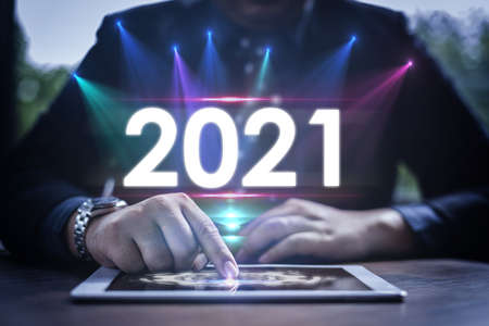 Digital infographic celebration 2021 year concept. Businessman uses a smart pad with a virtual screen and popup 2021 text.