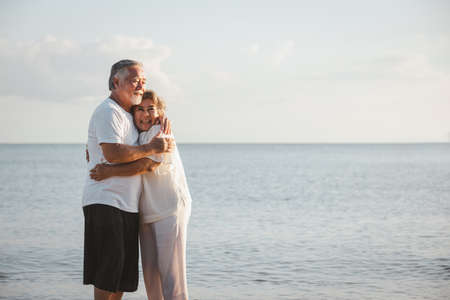 The romantic Asian senior couple hugging while standing on summer beach sunset. Travel leisure and activity after retirement on vacations and summer concept. Vacation and relaxation time. Zdjęcie Seryjne