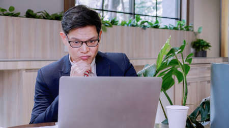 Attractive businessman thinking idea working his laptop at home office in living room, thinking, Professional looking away at laptop considering market risks, making difficult decision sit at desk. Stockfoto
