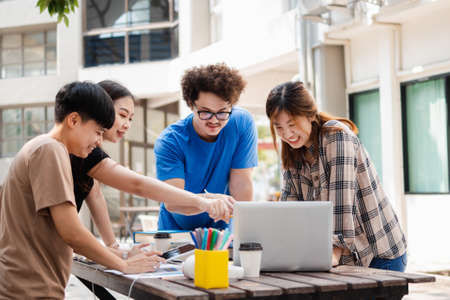 Happy Group of attractive young people using a laptop and tutoring together on study table, Social media online concept and Youth student and tutoring education with technology learning concept.