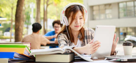 College student girl reading book for exam and listening to music via headphones with laptop. Youth student and tutoring education with technology learning concept. banner size Stockfoto