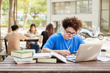 College student boy reading book for exam and listening to music via headphones with laptop. Youth student and tutoring education with technology learning concept.