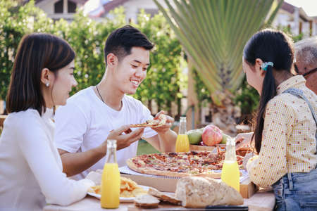 Happy asian family having enjoying meal(pizaa, salad,snack, orange juice) together in home garden. Outdoor dinner party in holiday. Multi generation family concept.