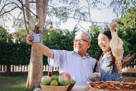 Asian retirement grandfather and pretty granddaughter enjoying to selfie while eating pizza together in home garden. Happy senior life after retirement with family concept.