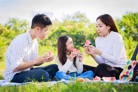Happy family picnic. Asian parents (Father, Mother) and little girl eating watermelon and have fun and enjoyed ourselves together during picnicking on a picnic cloth in the garden on a sunny day