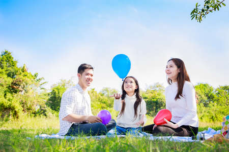 Happy family picnic. Asian parents (Father, Mother) and little girl playing balloon and have enjoyed ourselves together during picnicking on a picnic cloth in the green garden