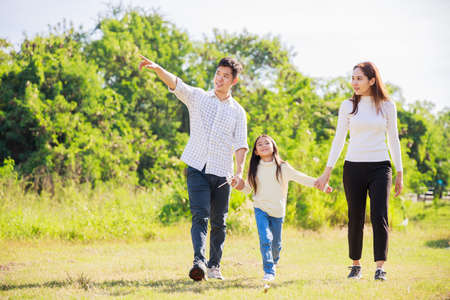 happy family life concept. Asian parents (Father, Mother) and the little girl walking and have fun and enjoyed ourselves together on a sunny day. family relaxes in the green park. Family weekend. Stockfoto