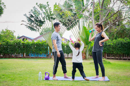 Fit happy people working out outdoor. Family Asian parent and child daughter exercising together on a yoga mat at home garden. Family outdoors. exercise at the home concept and new normal.