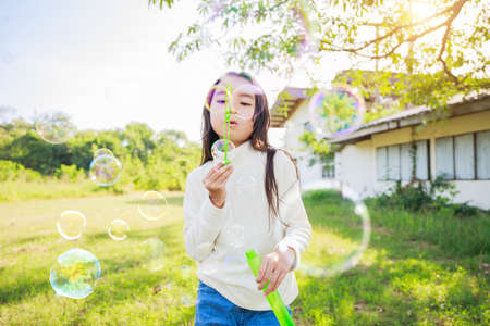 A little girl blowing soap bubbles with have fun and enjoyed on sunny days on weekend. Stockfoto