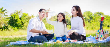 Happy family picnic. Asian parents (Father, Mother) and daughter playing the toy airplane and have enjoyed ourselves together while picnicking on picnic cloth in green garden in the sunshine day Stockfoto