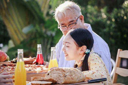 Asian retirement grandfather and pretty granddaughter enjoying to eating pizza together in home garden. Happy senior life after retirement with family concept. Stockfoto