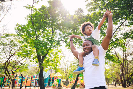 African American father giving son ride on back at park. family playing togetherness and relaxes. Family weekend. Cute African American boy with dad playing outdoor. Stockfoto