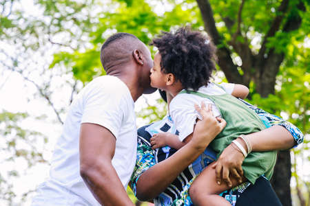 African American father and mother carrying his son and kisses on the cheek together with cheerful loving. Happy family.