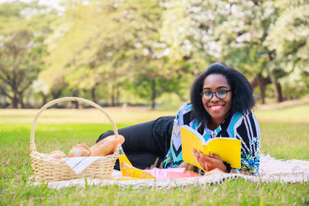 Happy young African American woman reading an interesting book. A cheerful African American woman in the park in the summertime. Young African American student