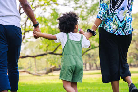 Happy African American family life concept. African American parents (Father, Mother) and little boy walking and have fun and enjoyed ourselves together. family relaxes in green park. Family weekend. Stockfoto