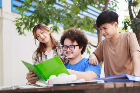 A happy group of attractive young people is tutoring exams with study books, sitting on the study table. Student group and tutoring education concept. Stockfoto