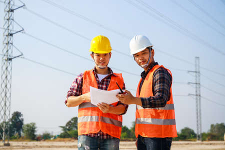 Portrait of Two Engineer, field engineer, foreman, owner standing in construction site project and Electric power line and pole in background. Asian engineer. High voltage power line pylon. Stockfoto