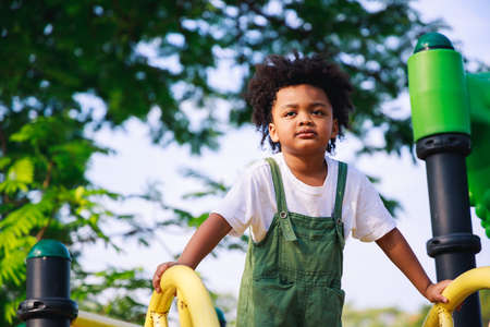 Cute African American little kid boy having fun while playing on the playground in the daytime in summer. Outdoor activity. Playing make believe concept. Outside education Stockfoto