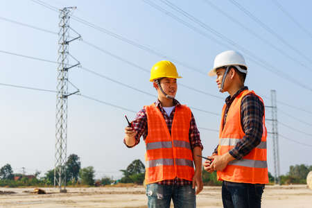 Asian engineer manager and foreman or leader discussion and pointing to construction site project on workplace and High voltage power line pylon in the background. Teamwork, Leadership concept. Stockfoto