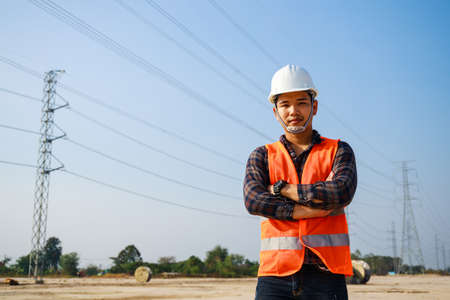 Portrait of Electrical Engineer, field engineer, foreman, owner standing in construction site project and Electric power line and pole in background. Asian engineer. High voltage power line pylon. Stockfoto