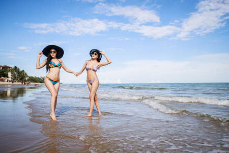Outdoor summer portrait of the front image of two Asian beautiful girls in a sexy bikini standing on the beach in summer. teenage girls best friends. sexy body. concept vacation, holiday in summer Standard-Bild