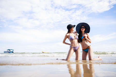 Outdoor summer portrait of the front image of two Asian beautiful girls in a sexy bikini sitting on the beach in summer. teenage girls best friends. sexy body. concept vacation, holiday in summer