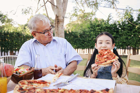 Asian retirement grandfather and pretty granddaughter enjoying to eating pizza together in home garden. Happy senior life after retirement with family concept. Standard-Bild