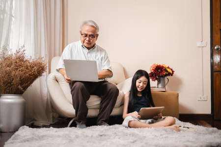 Asian retirement grandfather using a laptop and sitting on sofa while pretty granddaughter doing homework in tablet in living room. Family educational at home concept. Technology and education.