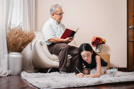 Asian pretty granddaughter doing homework while Asian retirement grandfather reading a book and sits on the sofa and rest in the living room. Family educational at home concept. Home school.