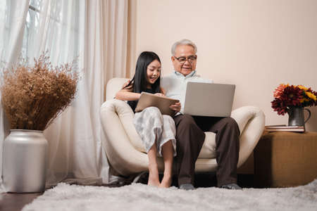 Asian retirement grandfather teaching homework pretty granddaughter by tablet and laptop in the living room. Happy Family educational at home concept. Technology and education.