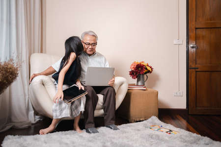 Asian pretty granddaughter kisses retirement grandfather cheeks while watching e-book for learning to education together by laptop. Happy Family educational at home. Technology and education.