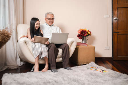 Happy Asian retirement grandfather and pretty granddaughter watching e-book for learning to education together by laptop. Happy Family educational at home concept. Technology and education. Standard-Bild