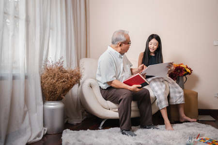 Asian retirement grandfather teaching and checking drawing on a paper with pretty granddaughter together while holding book and sits on the sofa in living room. Family education at home. Home school. Standard-Bild