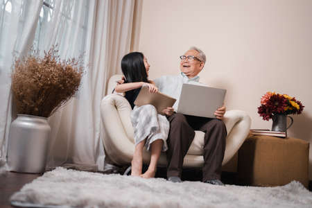 Happy Asian retirement grandfather and pretty granddaughter laughing while watching e-book for learning to education together by laptop. Family educational at home concept. Technology and education.