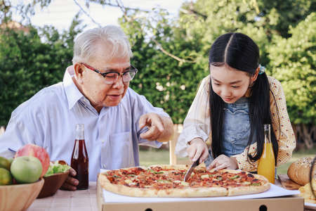 Granddaughter enjoying slicing pizza for retirement grandfather in home garden. Happy senior life after retirement with family concept. Standard-Bild