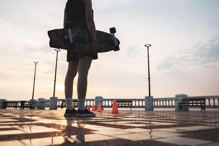Asian woman leg holding surf skate or skate board in outdoor Park at sunset. sport training for trendy people.