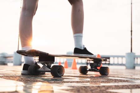 Asian woman leg on surf skate or skate board in outdoor Park at sunset. sport training for trendy people. Standard-Bild