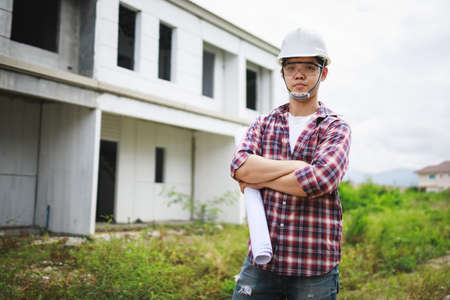 Portrait of Civil Engineer, field engineer, foreman, owner standing in construction site project in the background.