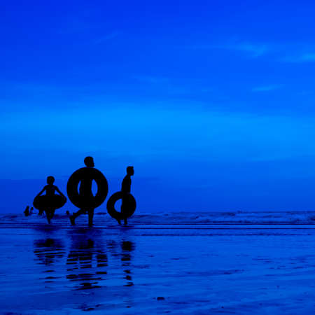 siluet people walking on the beach blue background Stock Photo