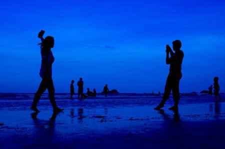 siluet: siluet people walking on the beach blue background Stock Photo