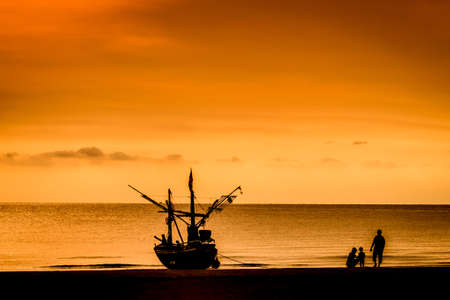 Fisher boat and family on Hua Hin beach  sunrise background Thailand