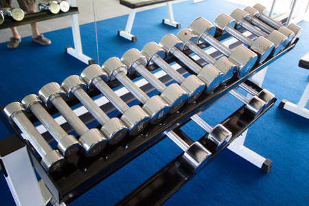 exert: Weights, many black dumbbell in fitness room Stock Photo