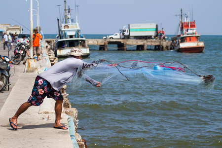 fisher man cast the mesh at Hua Hin fish pier Thailand Stock Photo - 15835814