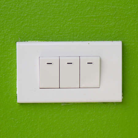 Electrical white rocker light switch on green wall photo
