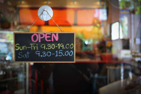 open time on the banner sign hang on the door in coffee shop